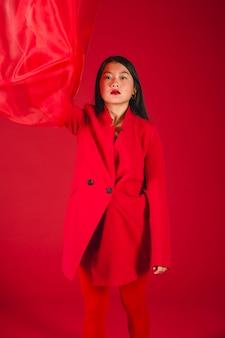 Schönes asiatisches modell, das in der roten kleidung aufwirft