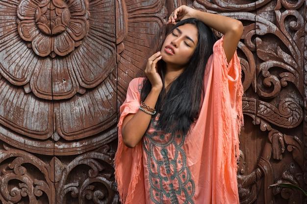 Schönes asiatisches modell im rosa boho-kleid, das über zierwand des holzes aufwirft.