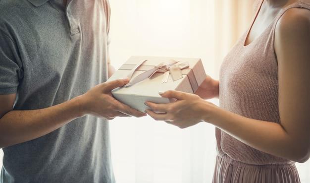 Schönes asiatisches paar, das geschenkbox-überraschungsjubiläum auf vorhanghintergrund hält. valentine people holiday festival konzept.