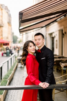 Schönes asiatisches paar, das hände hält und im café in der altstadt küsst