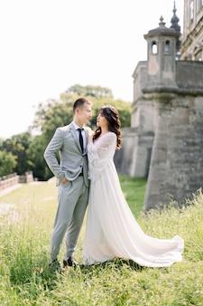 Schönes asiatisches paar, frau im hochzeitskleid, mann im anzug, posierend draußen nahe dem alten alten schloss