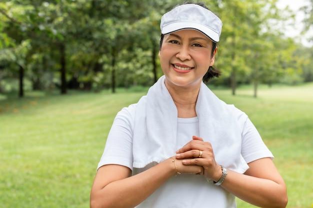 Schönes asiatisches porträt der älteren frau denkend und am park entspannend.