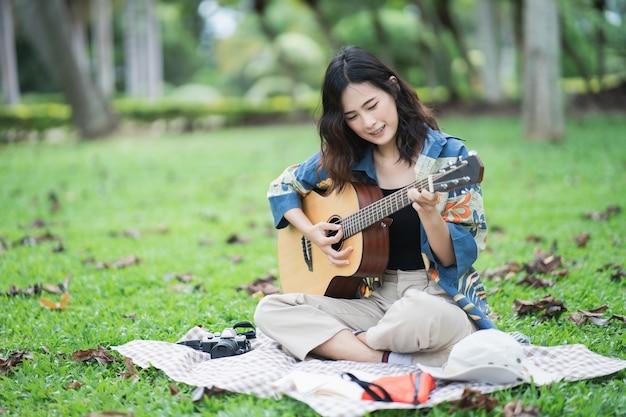 Schönes asiatisches studentenpicknick im park und denkendes komponierlied