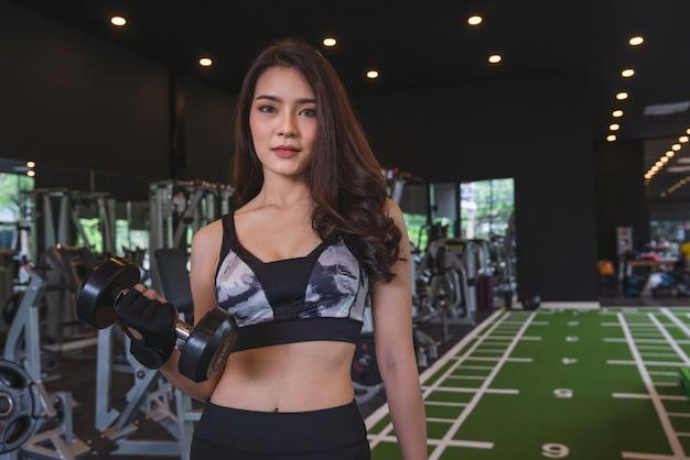 Schönes asiatisches trainingstraining und -übung der jungen frau mit dummkopfgewichten am eignungsturnhallensportverein