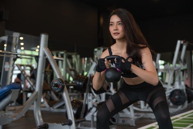 Schönes asiatisches trainingstraining und -übung der jungen frau mit kettlebell gewicht am eignungsturnhallensportverein