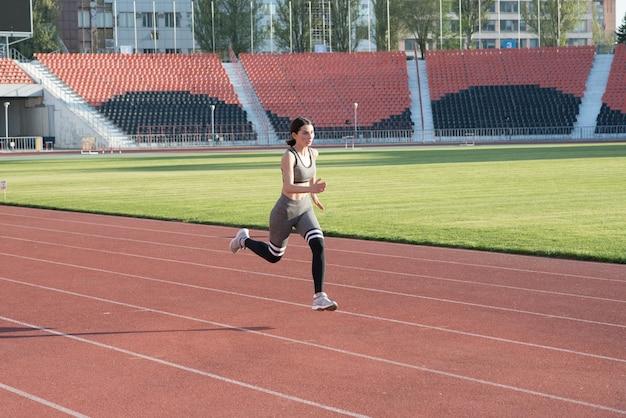 Schönes athletisches mädchen, das um das stadion läuft