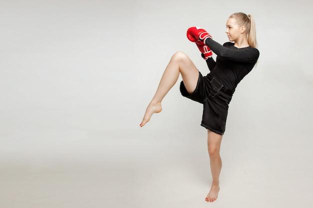 Schönes athletisches mädchen mit boxhandschuhen schlug hohen fuß.