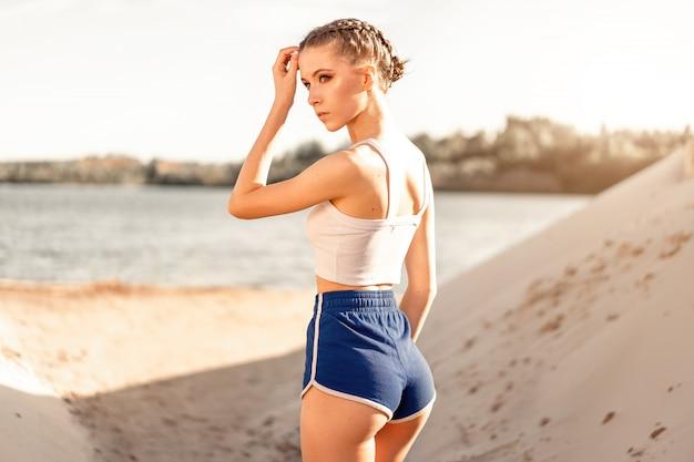 Schönes athletisches mädchen steht mit ihr zurück nahe dem see nach morgenübung. hintere ansicht der elastischen weiblichen hinterteile in den schönen sexy kurzen hosen