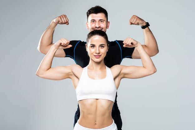 Schönes athletisches paar zeigen bizeps auf grauem hintergrund