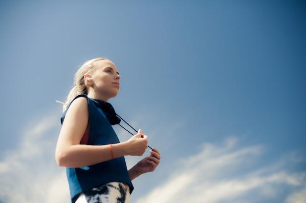 Schönes athletisches sitzmädchen in der hellen sport-kleidung, die nach dem training sich entspannt. sportart