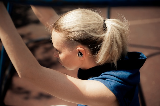 Schönes athletisches sitzmädchen in der hellen sport-kleidung, die nach dem training sich entspannt.