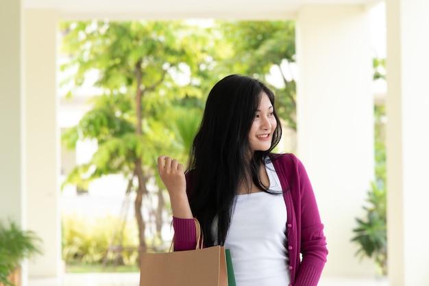 Schönes attraktives junges asiatingriff-einkaufstaschelächeln und glückliches im mall