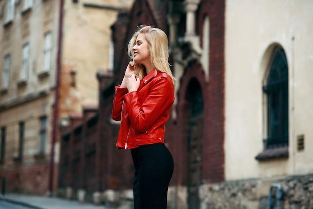 Schönes attraktives lächelndes blondes mädchen mit perfekter figur in einer roten lederjacke und im engen schwarzen rock