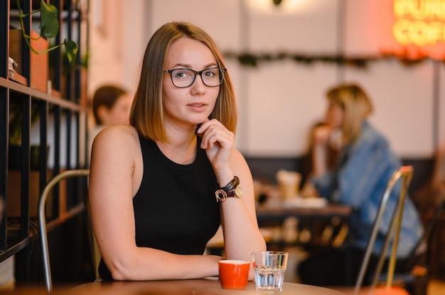 Schönes attraktives mädchen in der schwarzen brille. glückliches geschäftsmädchen, das in einem café arbeitet und am tisch sitzt