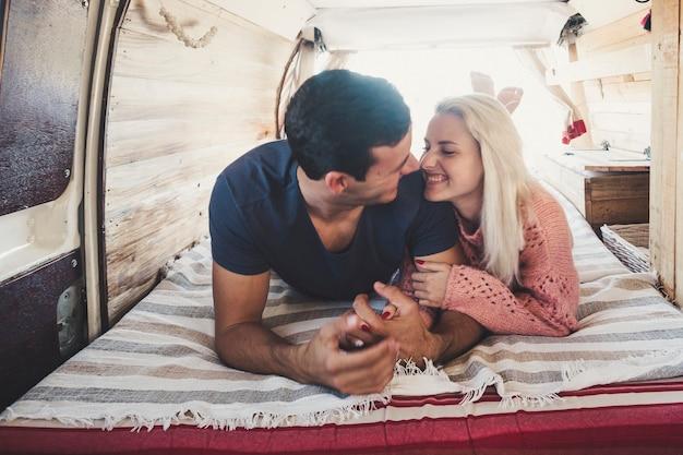 Schönes attraktives tausendjähriges verliebtes paar legte sich auf das bett in einem kleinen gemütlichen van, der perfekt ist, um zu reisen und den alternativen vanlife-urlaub auf der ganzen welt zu genießen