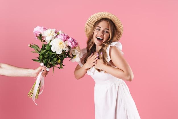 Schönes aufgeregtes junges blondes mädchen, das sommerkleid trägt, das isoliert über rosa wand steht und einen strauß pfingstrosen als geschenk bekommt