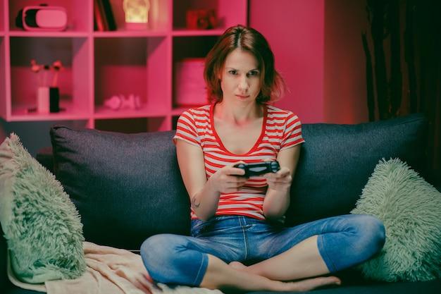 Schönes aufgeregtes junges spielermädchen, das auf einer couch sitzt und in videospielen auf einer konsole spielt.