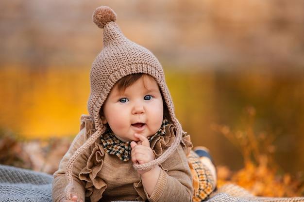 Schönes baby, das auf dem plaid nahe dem teich sitzt