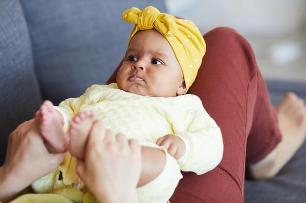 Schönes baby, das auf den beinen ihrer mutter liegt, während sie auf sofa zu hause ruhen