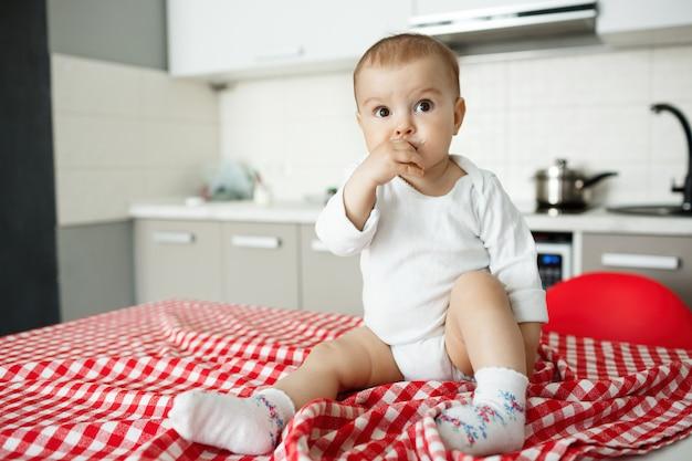 Schönes baby, das auf küchenschreibtisch sitzt und wegschaut