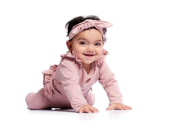 Schönes baby, das auf studioboden krabbelt