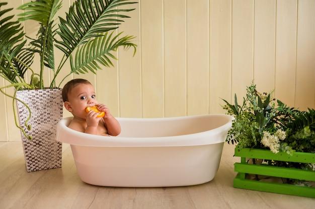 Schönes baby, das in einem bad sitzt und orangen auf einer holzwand isst