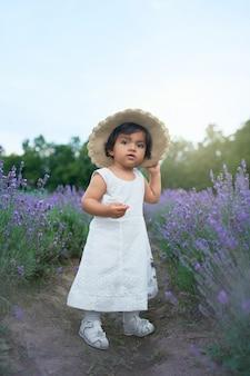 Schönes baby, das strohhut trägt, der im lavendelfeld aufwirft