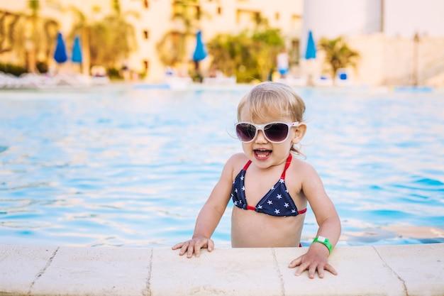 Schönes baby im pool, das glücklich in der sonnenbrille lächelt. wasser, meer, schwimmen, bikini, sommer, strand, resort
