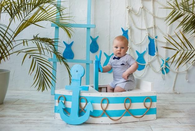 Schönes baby in einem gestreiften overall sitzt in einem blau-weißen holzboot und schaut in die kamera auf einer weißen wand mit platz für text