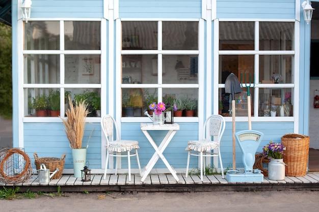 Schönes bauernhaus mit weidenkörben und grünen pflanzen auf der terrasse. weißer tisch und stuhl auf der veranda des hauses.