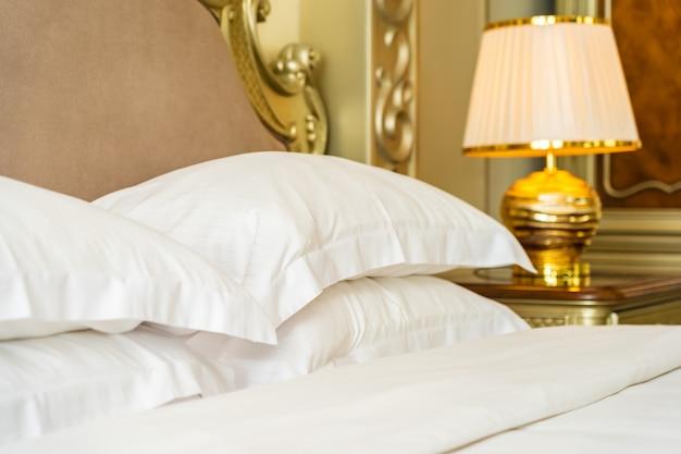 Schönes bequemes weißes luxuskissen auf bettdekoration im schlafzimmer