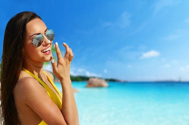 Schönes bikinimodell, das am tropischen strand mit ozeanhintergrund lächelt