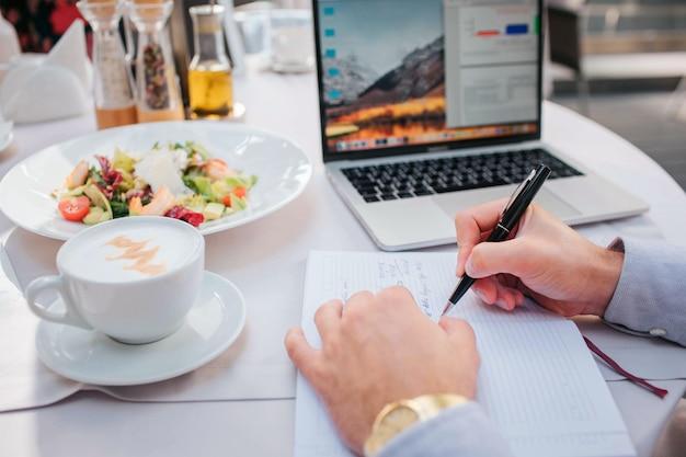 Schönes bild der hände des mannes, die stift halten. es gibt laptop, salat und kaffee am tisch. geschäftsmann bestellte essen zu essen. er ist beschäftigt. es gibt geöffnete notebbok am tisch.