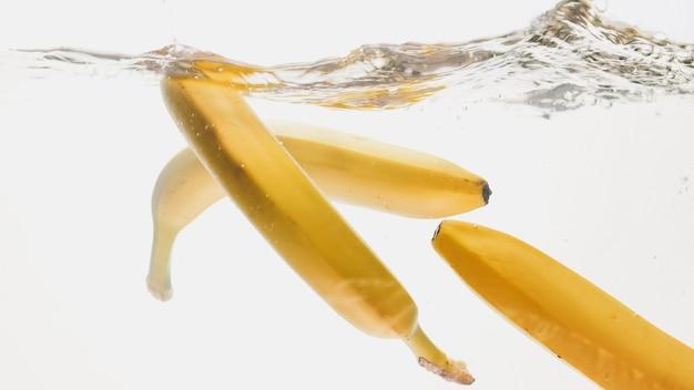 Schönes bild der nahaufnahme von bananen, die in klares wasser fallen