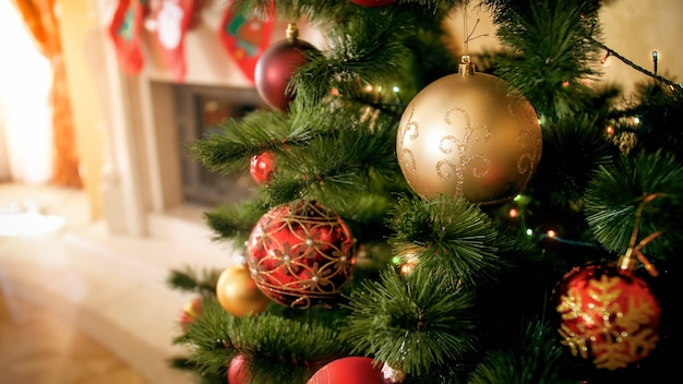 Schönes bild des geschmückten weihnachtsbaums mit roten und goldenen kugeln im wohnzimmer im holzhaus