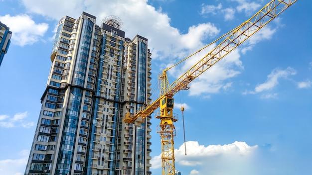 Schönes bild des hohen gelben baukrans auf der baustelle gegen hohes modernes gebäude aus beton und glas