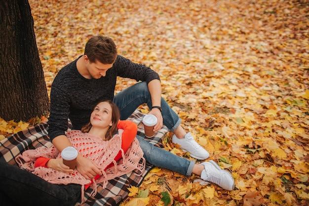 Schönes bild des jungen paares im park. frau, die auf decke liegt und mann ansieht. mann sitzt und schaut frau an. sie haben eine tasse kaffee.