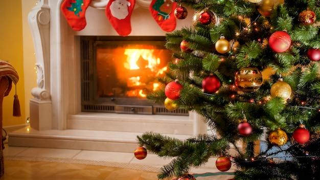 Schönes bild des weihnachtsbaums mit lichtern und kugeln gegen brennenden kamin im wohnzimmer