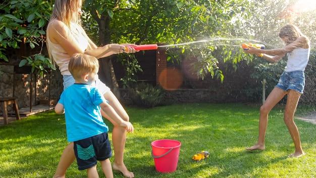 Schönes bild einer glücklichen lachenden familie mit kindern, die sich am heißen sommertag mit wasserpistolen und gartenschlauch amüsieren. familie, die im sommer im freien spielt und spaß hat
