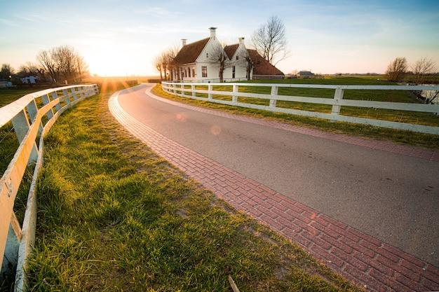 Schönes bild einer straße mit weißen zäunen neben dem haus bei sonnenuntergang