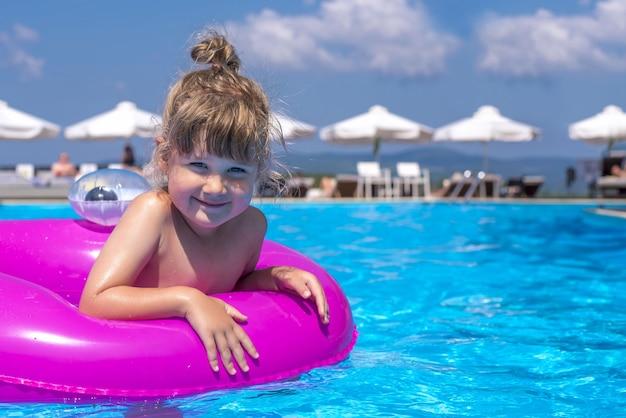 Schönes bild eines kindes in einem schwimmbad im sonnenlicht