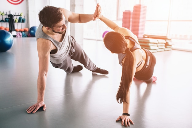 Schönes bild von jungen und mädchen, die in einer seitlichen plankenposition stehen und einander high-five geben.