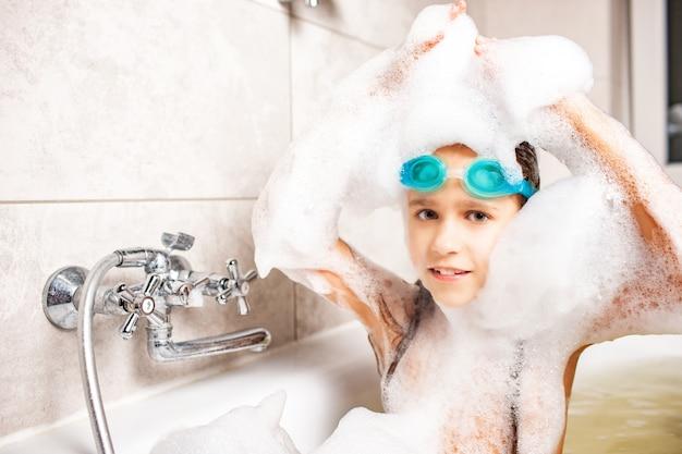 Schönes blauäugiges kleines mädchen in der schwimmbrille badet in einem schaumbad