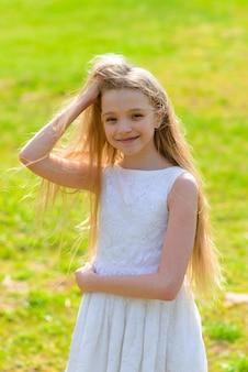 Schönes blauäugiges mädchen mit langen blonden haaren in einem weißen kleid, das blumengarten geht. sommer und frühling helles, emotionales foto.