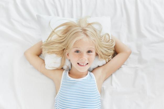 Schönes blauäugiges weibliches kind mit sommersprossen, auf weißem kissen liegend, hände dahinter haltend, angenehm lächelnd, froh, ihre eltern in ihrem schlafzimmer zu sehen. kleines mädchen, das im bett ruht