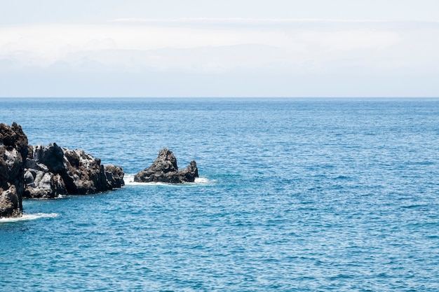 Schönes blaues meer mit felsen an der küste