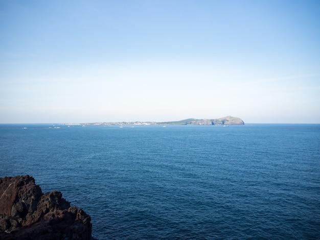 Schönes blaues meer mit schwarzem sandstrand und himmel von jeju-insel auf koreanisch
