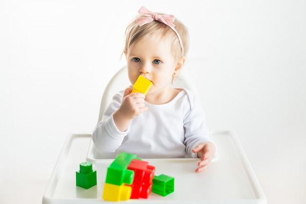Schönes blondes baby, das spiel mit spielzeug am kindergarten genießt, zeigt kinderhandhand auf bunten blöcken. kleinkind isolatd auf weißem hintergrund spielen