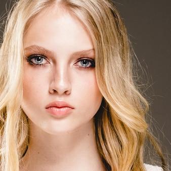 Schönes blondes frauen-schönheits-modell girl mit perfektem make-up und frisur über schwarzem hintergrund.