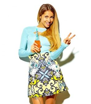 Schönes blondes frauenmädchen im zufälligen hippie-sommer kleidet ohne das make-up, das auf weißem trinkendem kolabaum von der flasche mit dem stroh getrennt wird, das friedenszeichen zeigt